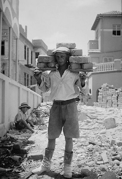Tel_Aviv_worker_carrying_bricks_1920-1930
