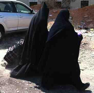 Two haredi burka cult taliban women, one with tube under head scarf
