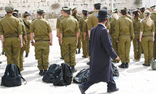 Haredi man walking past soldiers at Kotel