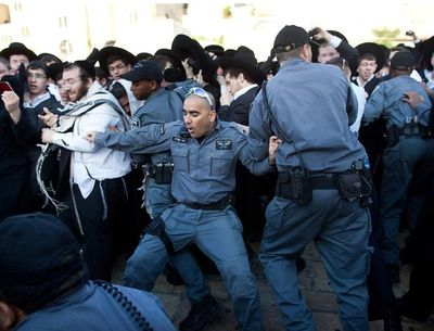 Police struggle to hold back a mob of haredi men who are trying to physically attack Women of the Wall members 5-10-2013