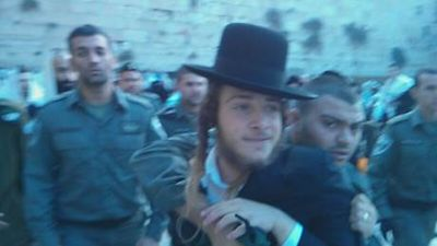 Hasidic man restrained by Border police at Kotel 12-4-2013 as he tries to attack Women of the Wall