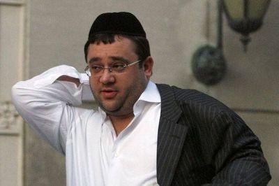 Eliyahu Weinstein no hat putting on coat