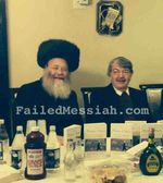 Joe Berger posing in hasidic sukka with his book 10-2014