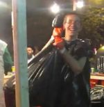 Teen Chabad hasid with bloody hands holds a trash bag full of dead chickens Kapparot Crown Heights 9-2015