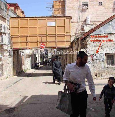 Unusual sukkah over street near anti-haredi IDF soldier graffiti Mea Shearim Jerusalem 9-2015