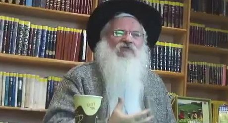 Rabbi Manis Friedman sitting in front of books